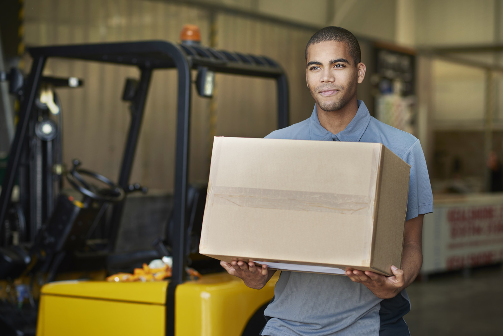 Young delivery man picks up parcels from  a factory. he is wearing industrial workwear and carrying a box on it. In the background an industrial unit can be seen with a forklift truck.