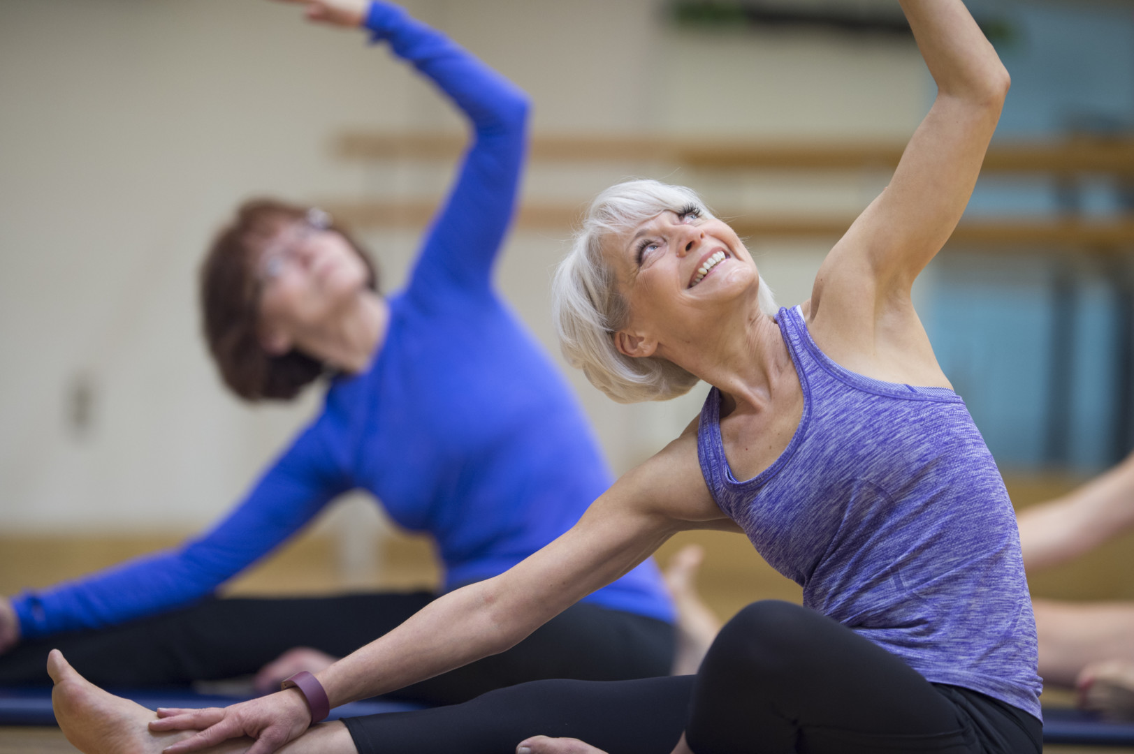 A multi-ethnic group of senior adult women are taking a yoga class together at the gym.